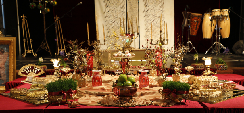 Haft Seen table photo, front view, decorated with red and golden foliage, vases, and jars