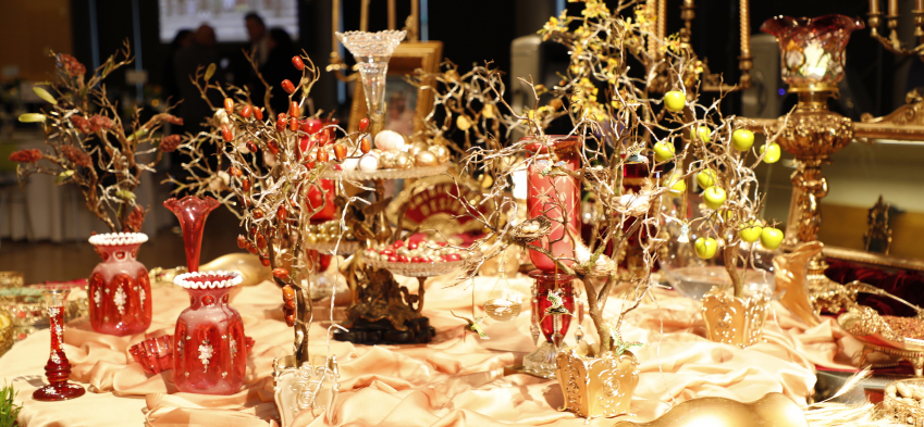 Haft Seen table close up photo decorated with red and golden foliage, vases, and jars