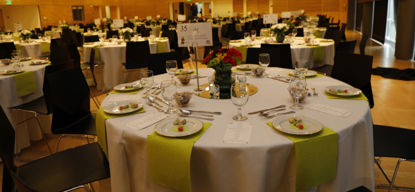 Nowruz table set up before event starts, plates of food, centerpieces, and ornamentation decorate each table