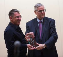 Ali Igmen receiving award from John Keeler, the dean of the Graduate School of Public and International Affairs at the University of Pittsburg